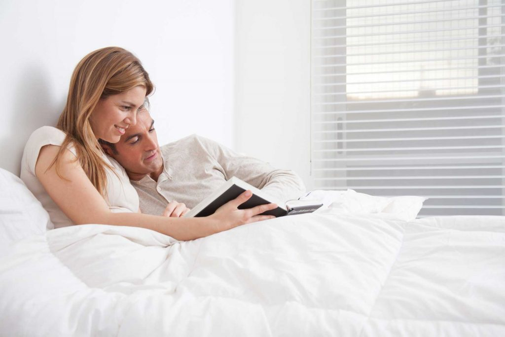 Couple in bed reading a book